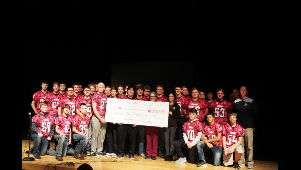 The Eleva-Strum football team recently donated the proceeds from this year's Tackling Cancer game to the Marshfield Clinic CLIMB program. Team members presented a check for over $2,500 to CLIMB coordinators Marcy Elwood and Nan Bethmann during a Cardinal Pride assembly on Oct. 25.