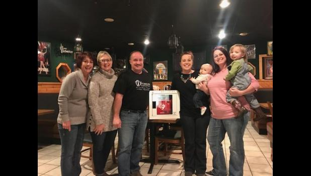 "Mondovi Police Chief Colin Severson (center left) accepted the donation of a new AED unit from the family of Steven D. Larson of Donnelly, Minn., on Nov. 23. The AED was gifted by the non-profit group ""Papa's Angels."""
