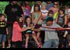 Eleven-year-old Bella Tiegs (center) prepared to do the honors at the ribbon-cutting event with help from her dad, Jeff Tiegs, and Jessica Kummer, Kylynn's mother.