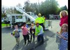 The Bucket Truck from Tri County Electric caught the students eyes when the employee/ driver showed how the boom box could go up and down and sideways to get at the lines that might need repair or maintenance. He points out some of the electric lines by the school grounds that he sometimes may have to work on when the power may go down.  Photo by Carol Boynton