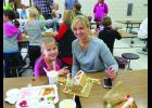 Check out all the Gingerbread houses being made on PG 14 as a tasty tradition by the first graders.  Here, Macie and her mom, Jess Jonsgaard are getting their Gingerbread House all ready for the Christmas table.  Photo by Carol Boynton